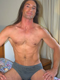 sporty-long-haired-brunet-gay-strips-nude-and-shows-it-all-in-the-middle-of-a-bed