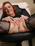 mature-redhead-strips-down-to-her-black-lingerie-and-spreads-her-pussy-lips