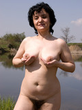 naughty-brunette-mature-demonstrates-her-big-shapeless-tits-and-bush-by-the-lake