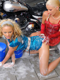 two-blondes-dressed-in-red-and-blue-get-wet-from-top-to-toe-while-washing-a-bike