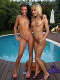 Two petite girls with tiny asses pose naked by the pool and then try strapon sex