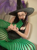 glassed-halloween-girl-in-hat-and-striped-black-and-green-pantyhose-licks-her-feet