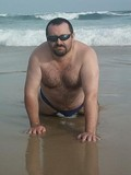 fat-hairy-chested-bear-in-shades-poses-nude-in-wet-sand-on-the-wild-beach