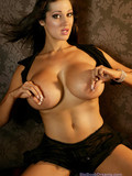 glamorous-brunette-with-monster-tits-gets-naked-in-the-semi-dark-of-the-room