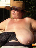 fat-woman-in-hat-gets-her-monster-tits-out-while-sitting-on-a-bench-in-the-sun