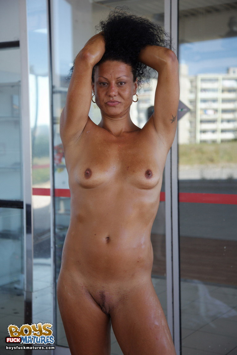 tanned mature brunette with small breasts and trimmed pussy strips nude