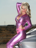 perfect-bodied-blonde-in-tight-fit-purple-latex-suit-poses-outside-beside-silver-sports-car