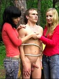 two-wild-girls-tie-guy-to-the-tree-and-play-with-his-helpless-cock-in-the-woods