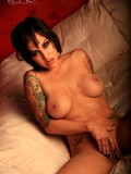 tattooed-well-stacked-brunette-regan-reese-in-boots-strips-out-of-her-bikini