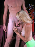 Blonde girl in green outfit sitting on knees and deepthroating the guy's dick