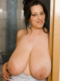 Topless brunette with massively huge heavy naturals doing her face in the bathroom