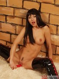 brunette-haired-fetish-model-in-high-latex-boots-spreads-her-long-legs-wide-open