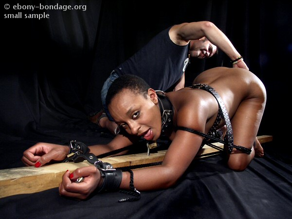 ebony slave girl - Restrained dark skinned slave girl with oiled body gets her pussy toyed by  white master
