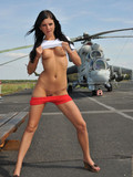 leggy-brunette-with-big-tits-takes-off-her-red-shorts-in-the-middle-of-the-airfield