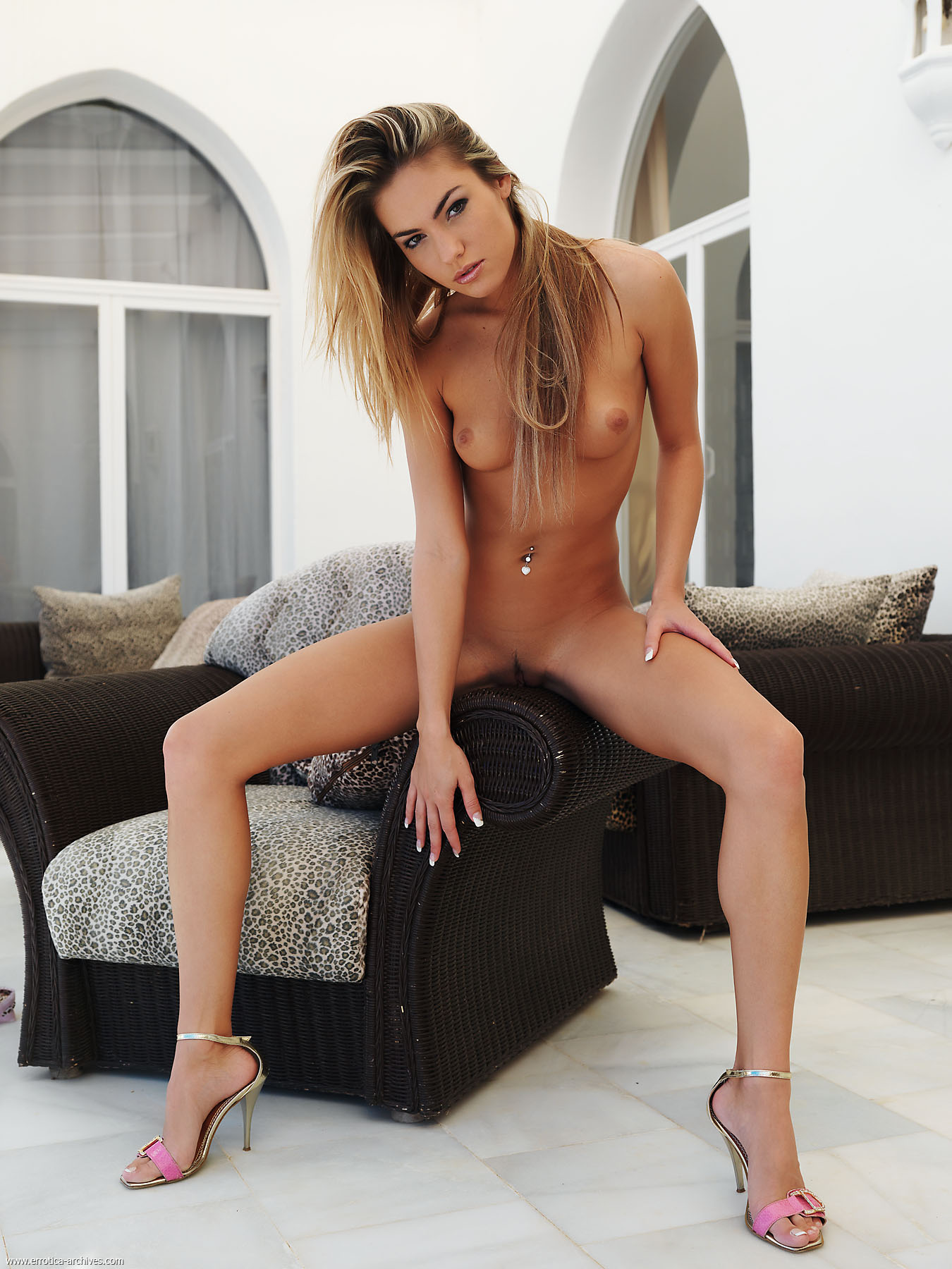 slender naked seductress with long hair and legs demonstrates her
