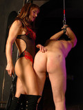 clothed-mistress-in-boots-makes-naked-slave-guy-bend-over-and-punish-him-with-no-mercy