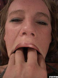 blonde-in-short-black-skirt-stretches-her-mouth-and-pussy-with-all-five-fingers