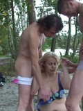 Two men fuck big breasted chubby blonde granny on the bank of the river