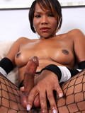 Dark skinned shemale in black fishnet pantyhose takes off her striped dress and shows her dick