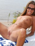 long-haired-sunglassed-nude-girl-with-bald-pussy-and-hairy-arms-spreads-her-legs-on-the-beach
