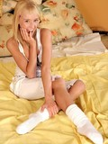 naughty-teen-blonde-gives-playful-smile-while-sticking-yellow-toy-in-her-tiny-hole