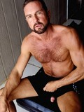 Hairy chested bearded gay bear poses in white jocks and flashes his pistol
