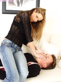 Graceful girl in skin tight blue jeans sitting on guy and smothering him