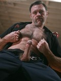 Older man with hairy chest and pierced nipples strips out of his black uniform