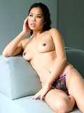 Delicious asian dressed in lingerie pulls off her bra to display her bare tits