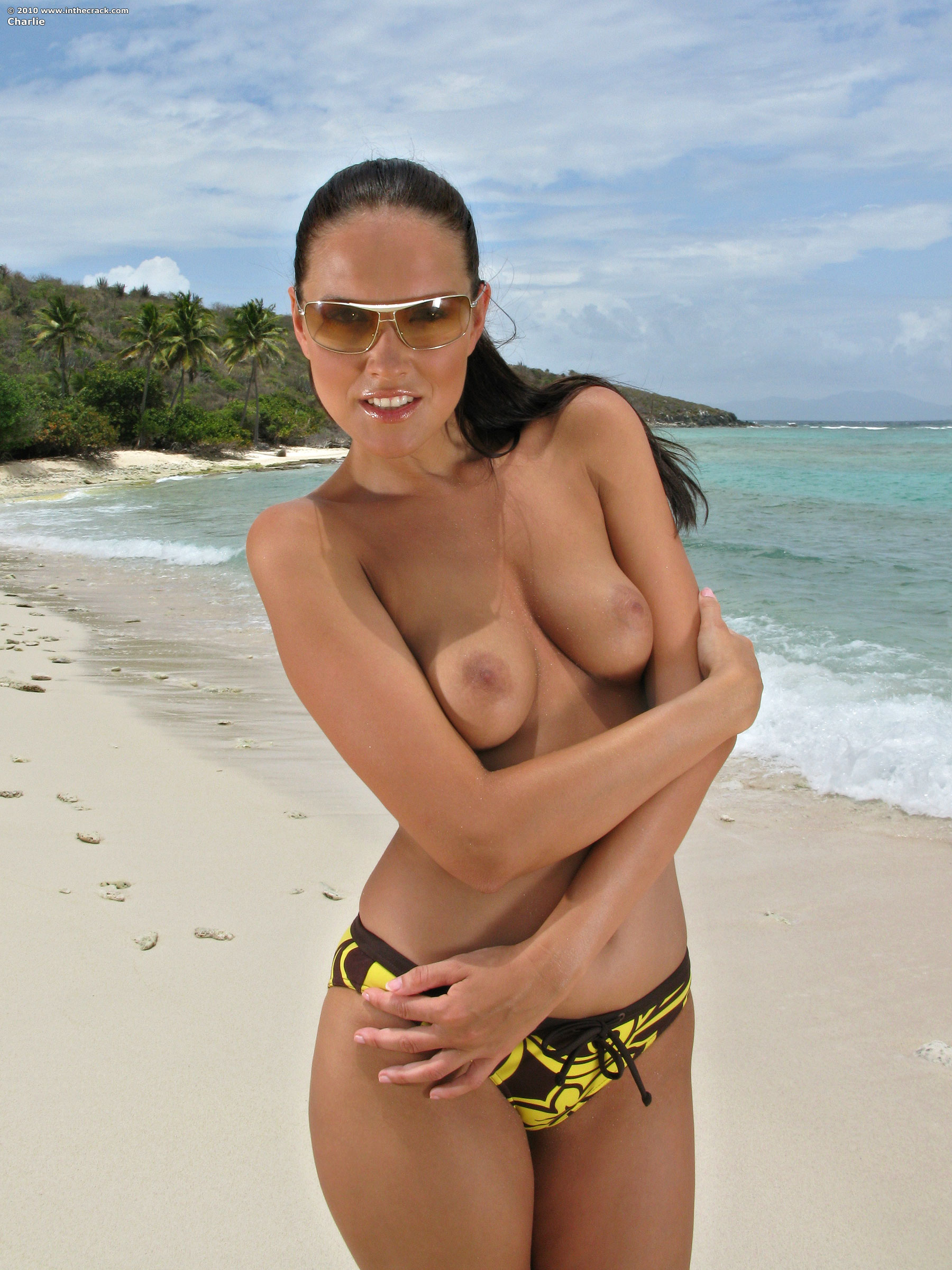 Wet beauty takes off her bikini and shows her tiny hole in sand on exotic beach