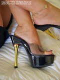 woman-in-short-black-skirt-gives-a-close-up-view-of-her-feet-and-high-heels-on-a-bed
