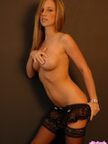stocking-temptress-in-black-lingerie-takes-off-her-corset-and-palms-her-tits