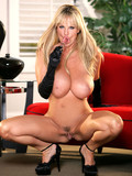 High heeled busty Kelly Madison in long gloves takes off her black bra and panties