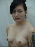 dark-haired-girl-with-tattooed-arm-takes-off-her-black-bra-and-shows-her-tiny-nipples