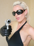 well-heeled-blonde-in-black-gloves-dress-and-shades-poses-with-gun-in-hand