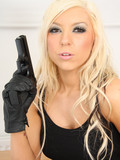 very-attractive-slim-white-haired-babe-dressed-in-black-poses-with-gun