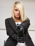 blonde-dressed-in-black-and-white-holds-her-gun-tightly-while-posing-for-you