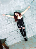 long-haired-redhead-in-black-latex-dress-and-high-boots-is-ball-gagged-and-chain-bound