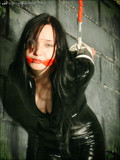 high-heeled-gagged-brunette-in-black-latex-outfit-gives-strappado-bondage-a-try