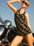 blonde-haired-model-in-sunglasses-and-short-dress-poses-beside-the-bike-at-the-ocean-side