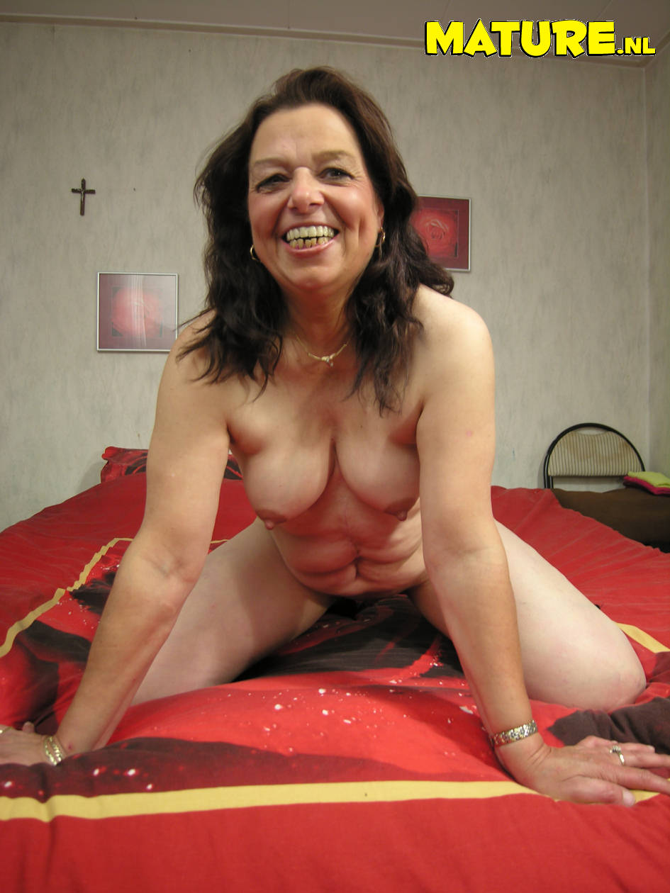 mature brunette strips down to her boots and plays with her loose