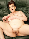fat-spectacled-mature-lady-in-white-blouse-and-black-skirt-gets-naked-and-plays-with-dildo