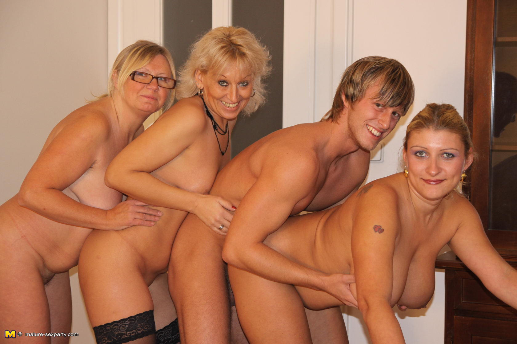 horny dudes at the party - Handsome blond guy is sandwiched between thee sex crazed matures who want  his dick badly