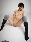 slim-brunette-model-in-ultra-short-dress-and-knee-highs-exposes-her-tiny-bare-ass