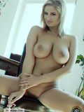 naked-sexy-legged-blonde-babe-touches-her-beautiful-big-sized-boobs-on-a-chair