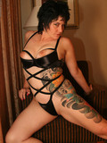 short-haired-brunette-in-black-lingerie-shows-her-color-tattoos-in-the-bedroom