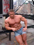 strong-topless-man-in-tight-blue-jean-shorts-shows-off-his-iron-muscles-outdoors