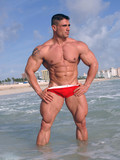 handsome-bodybuilder-proudly-shows-his-big-iron-muscles-at-the-beachside