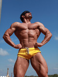 black-haired-muscle-man-poses-in-tight-yellow-shorts-and-plays-with-his-prick