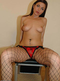 brunette-in-black-fishnet-stockings-takes-off-her-red-mini-skirt-and-panties-to-show-her-snatch